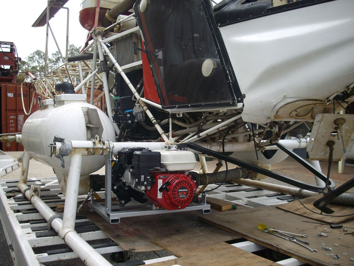The fuel tank for the spraying equipment is mounted on a custom made platform hung from a support suspended between the helicopters undercarriage and the strut for the landing ski.