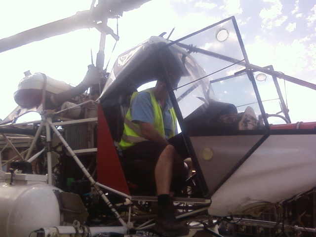 A Spray Shop technician testing the spaying machinery in crop-dusting helicopter custom built by the Spray shop