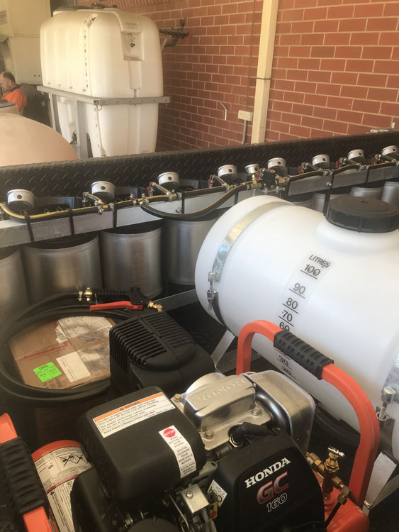 Inside view of the Trial Plot spray trailer showing the 10 chemical mixing cylinders the Honda generator and the water supply tank