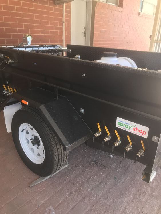 Side view of Trial Plot spray trailer showing the overflow outlet taps