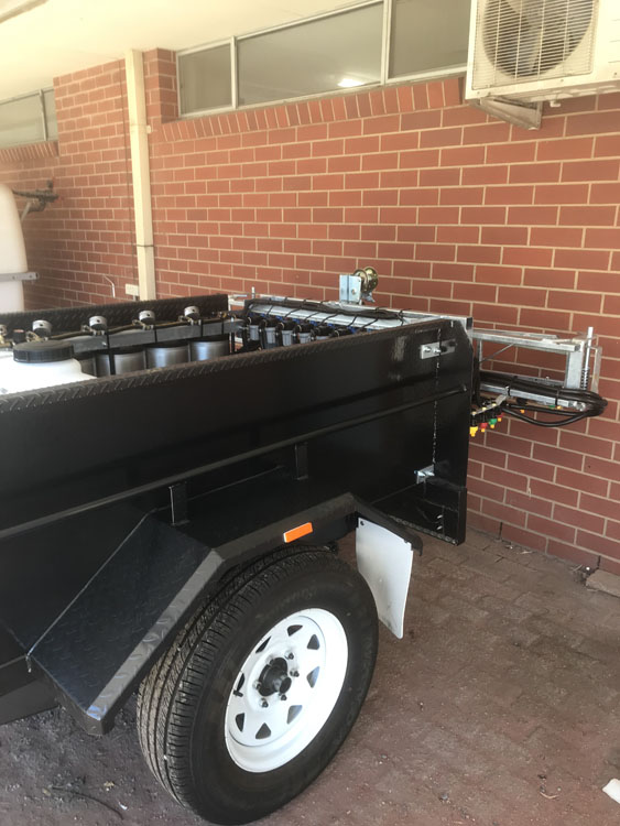 Side view of the Trial Plot spray trailer showing the collapsed extendable spray arms